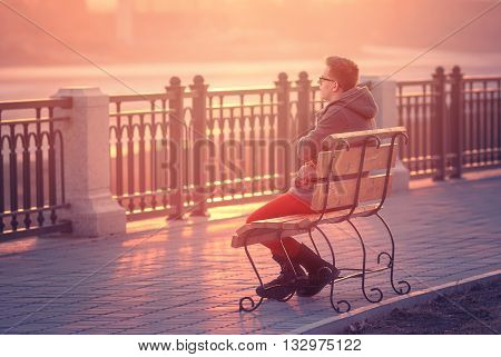 Photo of Lonely Man Sitting on a Bench during Sunset. Young Man Sitting on Wooden Bench. Sunset Male Outdoor Background