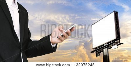 Businessman using smartphone with blank billboard for copy space on beautiful sky