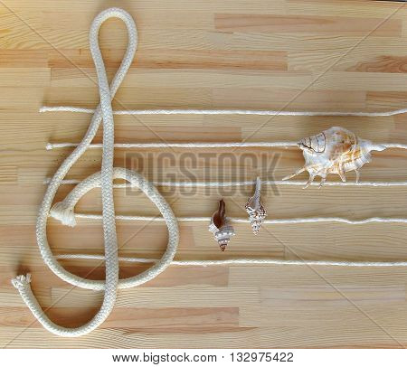 Treble clef and stave made with white ropes on the deck with seashells