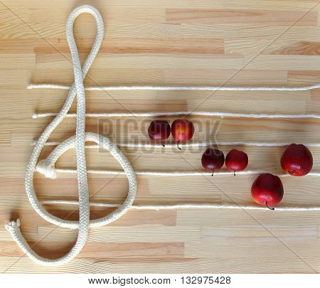Treble clef and stave made with white ropes on the deck with apples