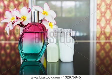 Single bottle of sweet fragrant perfume with group of mini spa bottle set on luxury vintage background and pink flower plumeria or frangipani relax luxury mood perfume and spa shower bath gel set in boutique and classic mood background