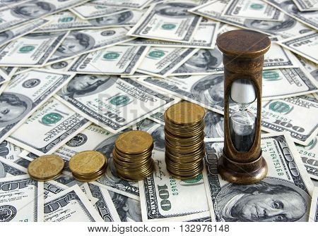 Golden coins and hourglass placed on a surface covered with dollar bills symbolize Time is money concept