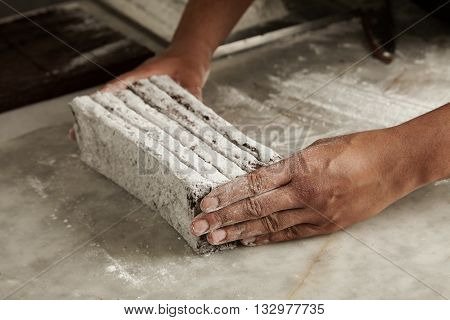 Hands Of Black Man Chief Holds Freshly Baked Chocolate Bars In Sugar Powder Before Packing, Closeup