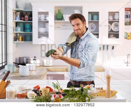 Happy man having fun in kitchen, acting like action hero, using cucumber as gun.