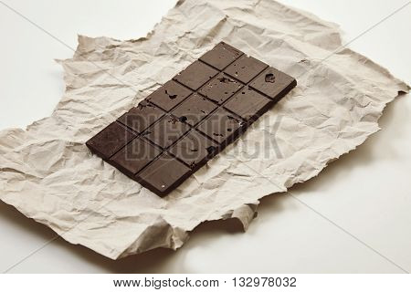 Artisan Homemade Organic Healthy Chocolate Bar On Craft Paper, Isolated On White Table, Side View