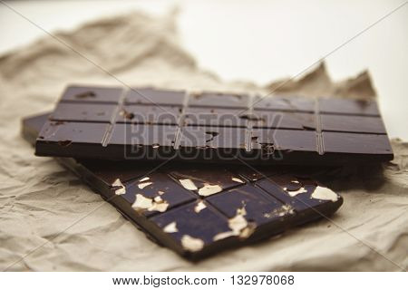 Close Up On Two Different Rustic Chocolate Bars Freshly Baked , On Craft Paper, Isolated On White Ta