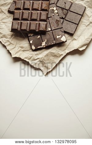 Three Different Homemade Organic Natural Artisan Chocolate Bars On Rustic Craft Paper Isolated On To