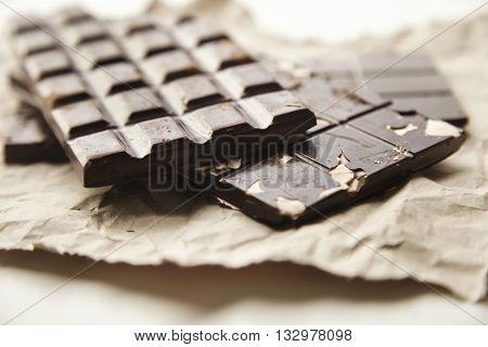 Closeup Focus On Three Different Homemade Organic Natural Artisan Chocolate Bars On Rustic Craft Pap