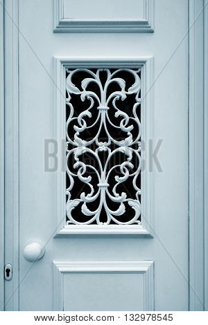 Detail of a baroque style decorative window on a white door