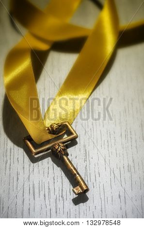 Old skeleton key with yellow thick ribbon over white wooden surface