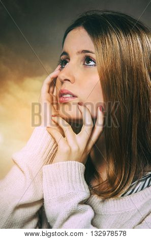 Studio portrait of a pretty blond teenager girl with hand in her face