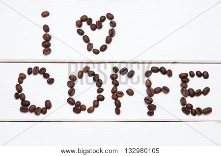 Coffee beans arranged in the word i like coffe on white wooden