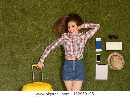 Happy beautiful tourist lady lying on green grass and holding yellow luggage. Pretty woman with red lips lying among mobile or smart phone, passport, cap, map or guide, etc.