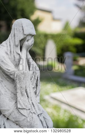 Statue of a desperate woman. Defocused blurry background.