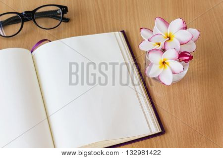Plumeria or frangipani flowers in glass with blank note book and fresh relax mood empty note book with frangipani or plumeria flowers on work table for copy space area blank page diary on wooden table