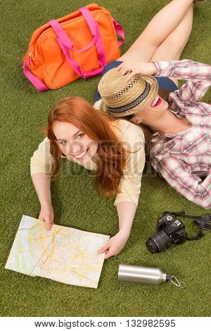 Picture of beautiful tourist ladies lying on green grass. Tourism concept. Happy women resting and relaxing on outskirts or urban area.