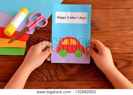 Child holds a greeting card in his hands. Kids crafts for father's day. Card with message Happy father's day. Holiday gift for dad. Sheets of colored paper, scissors, glue stick. Wooden background
