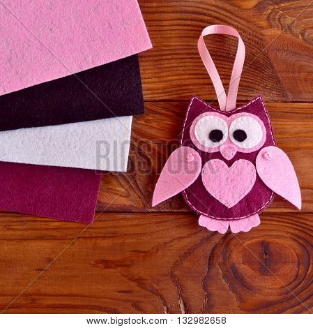 Funny maroon felt owl with a pink heart. Gift idea for Valentine's day, 8 March. Cheap and easy decorating idea. Sewing workplace. Burgundy, pink, white and black felt texture. Brown wooden background