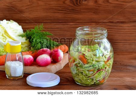 Vegetable salad in a glass jar. Salad of radish, carrots, cabbage, olive oil, salt and dill. Green dill leaves, fresh carrot, cabbage, radishes on a cutting board. Wooden background. Healthy diet food