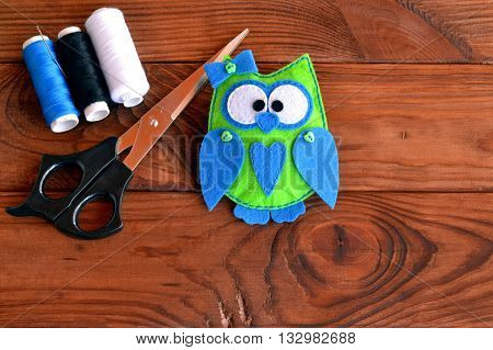 Funny bird felt toy, a set of threads, scissors on a wooden table. Stitched baby felt owl. Crafts sewing felt. Stuffed owl sewing pattern. Fabric owl plush softie. Art and handcraft for kids