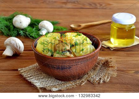 Baked potatoes with mushrooms and dill in an clay bowl. Homemade slow cooker braised potatoes with mushrooms. Olive oil in a glass jar. Little wooden spoon. Dill, fresh mushrooms. Wooden table.