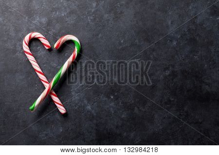 Candy canes heart over stone background. Top view with copy space