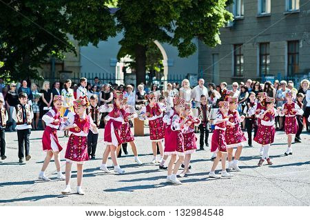 Bila, Ukraine - May 27, 2016: School Line Is In Schoolyard With First-grade Pupils And Teacher. Scho