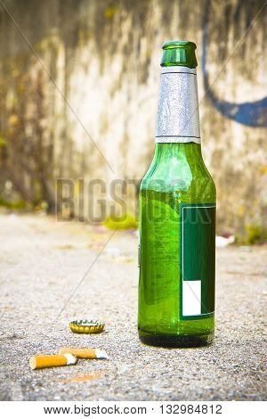 Bottle of beer resting on the ground with three cigarette's butts. Alcoholism and tobacco addiction concept
