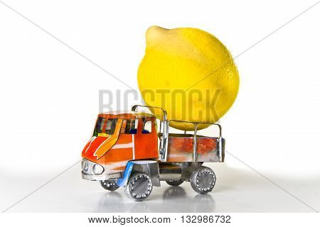 Small lorry loaded with one big lemon - concept image
