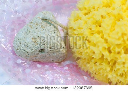 Pumice to remove hard skin and natural sponge in yellow on a background of shower caps pink color