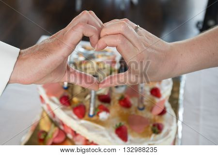 Couple In Front Of Cake Making A Heart With Hands