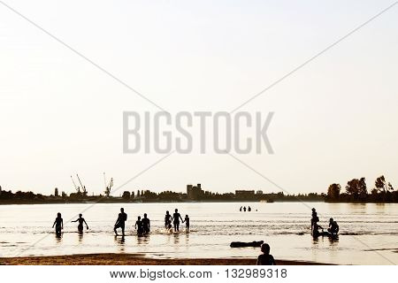 People silhouette on a river beach with city industry landscape in the background