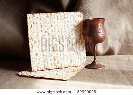 Seder concept. Still life with matzoh near metal wineglass