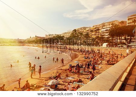 CANNES FRANCE - JULY 5 2015: The beach in Cannes. Cannes located in the French Riviera. The city is famous for its Film Festival. FRANCE - JULY 5 CANNES 2015