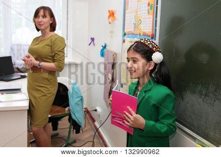 Ashgabad Turkmenistan - November 4 2014. Schoolgirl telling lesson at the blackboard. November 4 2014. In schools of Turkmenistan annually trains about 900 thousand children.