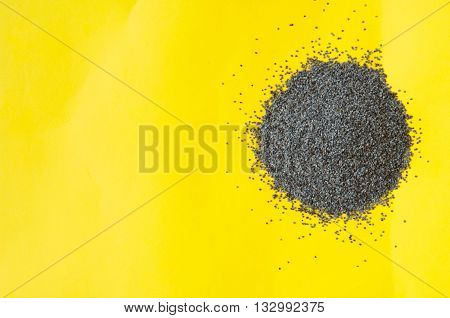 Poppy seeds isolated on yellow background poppy seed pile of poppy seeds
