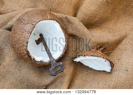 Rusty metal key found in cracked coconut shell on old jute cloth background as a clue for pirate treasure