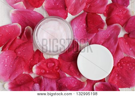 Cosmetic cream container, top view, rose petals water drops scattered background. Aromatic skin care balm.