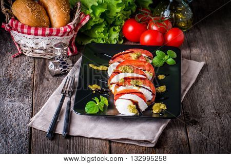 Caprese Salad on black plate - Salad with Tomatoes, Mozzarella Cheese, Basil and Balsamic. Salad Dressing with Pesto Sauce