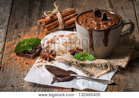 Mug of hot chocolate with cinnamon sticks over dark wooden background.