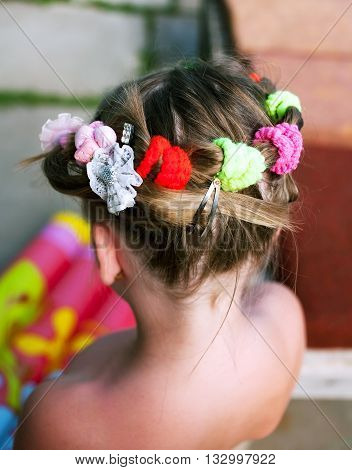 Children's hair with tightening rubber bands and bobby pins rear view