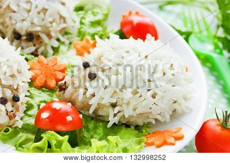 Food art idea for children healthy dinner: steamed hedgehogs meatballs on vegetable garnish glade selective focus