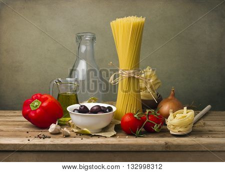 Italian food concept. Pasta and vegetables on wooden tabletop against grunge wall.