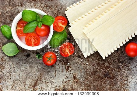 Lasagna pasta cherry tomatoes and basil on old metal background blank space for text recipe top view