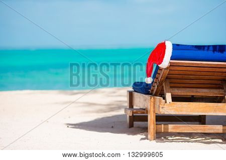 Sun chair lounger with red Santa Hat on tropical white beach and turquoise water