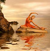 Постер, плакат: Красивая молодая женщина делает йога упражнения на открытом воздухе