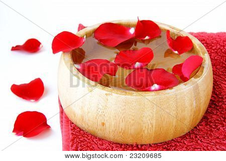 spa concept with rose petals and a red towel