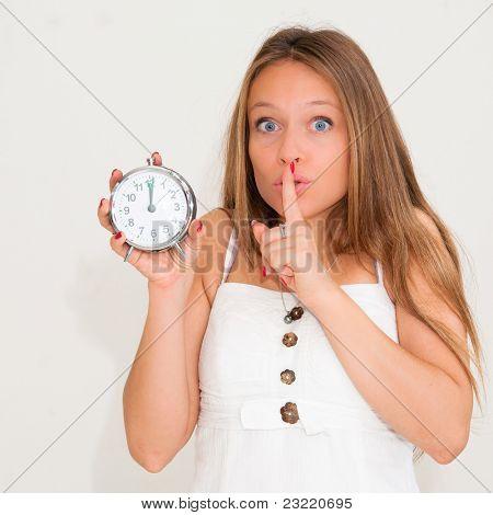 beautiful young woman holding alarm clock and hushing