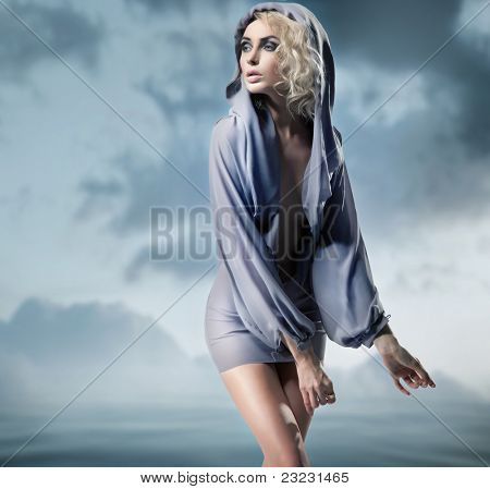 Blond beauty posing over dark sky