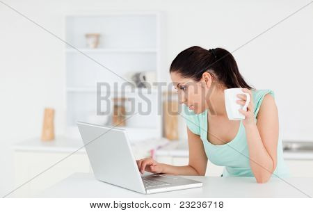 A beautiful young woman is holding a cup of coffee whilst typing on her laptop